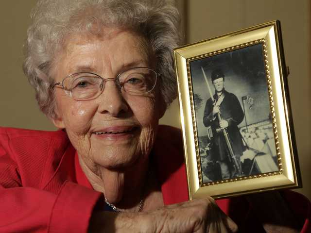 Juanita Tudor Lowrey, age 86, poses with a photo of her father, Civil War veteran Hugh Tudor Tuesday, March 19, 2013, in Kearney, Mo. Lowrey received pension benefits related to her father's Civil War service until she was 18 after her father died when she was 2 years old.