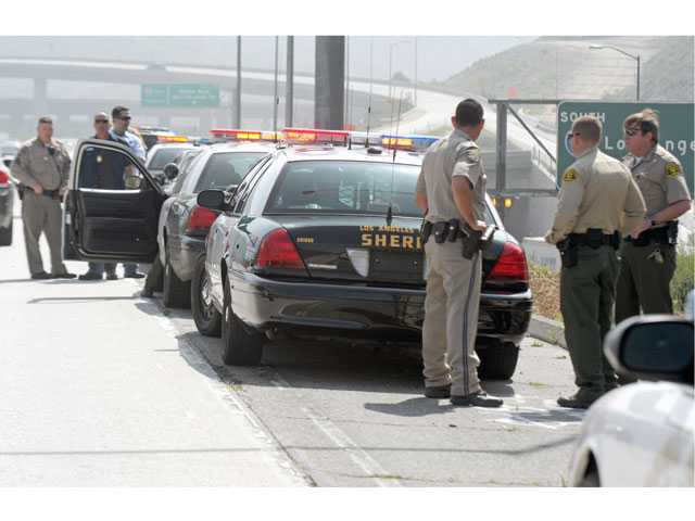 Deputies from the Santa Clarita Valley Sheriff's Station and California Highway Patrol officers work in lanes on southbound Interstate 5 at Highway 14 after authorities made a felony stop Tuesday morning.