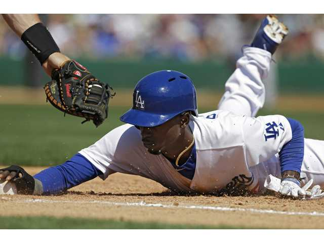 Los Angeles Dodger Dee Gordon dives under the tag from Arizona Diamondbacks first baseman Paul Goldschmidt on Monday in Glendale, Ariz.