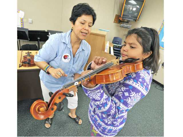 "Third-grader Monica Sanchez, right tries out the violin with volunteer parent and musician Julissa Bozman in an ""Instrument Petting Zoo"" at Wiley Canyon Elementary School in Newhall on Tuesday. (Jonathan Pobre/The Signal)"