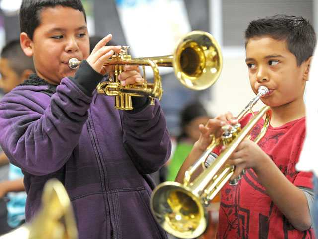 "Third-graders Orlando Hernandez, left, and Gabriel Torres play trumpets in an ""Instrument Petting Zoo."" (Jonathan Pobre/The Signal)"