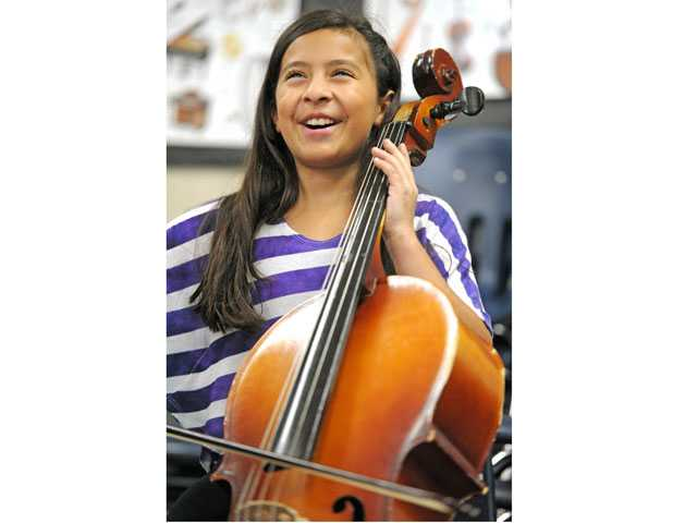 "Fourth-grader Aliyah Valencia enjoys a moment with a cello in an ""Instrument Petting Zoo."" (Jonathan Pobre/The Signal)"