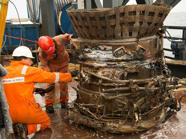 In this image provided by Bezos Expeditions, workers inspect a thrust chamber of an Apollo F-1 engine recovered from the bottom of the Atlantic Ocean in March 2013. An expedition led by Amazon CEO Jeff Bezos pulled up two rocket engines, including this one, that helped boost Apollo astronauts to the moon.