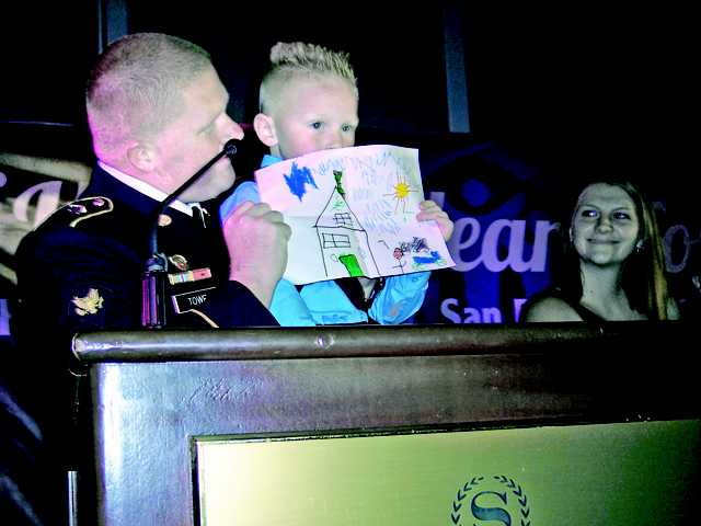Ethan Towe, held by his father Joshua Towe, displays a picture he drew of what he hopes his new home will look like in Veterans' Village.