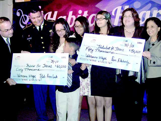 """Officials from Citibank, Habitat for Humanity and veterans and family members display checks presented to the """"Hearts for Heroes"""" campaign."""