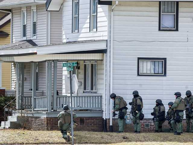 Armed officers surround a house Wednesday, in Fort Wayne, Ind., where police say a man suspected of killing a bus passenger earlier in the day is holding a 3-year-old child hostage.