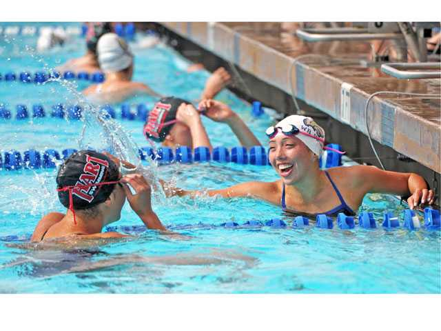 Hart's Tamara Santoyo, left, congratulates West Ranch's Taylor Poliseno after she wins the 50-yard freestyle on Wednesday at the Santa Clarita Aquatic Center.