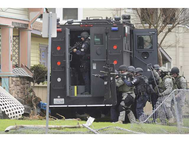 A SWAT team gets ready to enter a house on the corner of Illinois and Sutter Streets in Vallejo on Wednesday during a long stand off between a man barricaded inside the house and police.