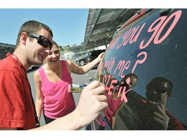 "Erik Cordes, left. signs his name after Cheyenne Davenport helps him write a prom invitation on the windows of his intended date's SUV on Friday. The Saugus High School student surprised Kelly Cooksey with the proposal after cross country practice. She said ""yes"" via Twitter. Signal photo by Jonathan Pobre"