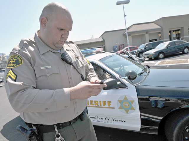 "Deputy Josh Dubin Posts a tweet about an incident he worked in the Vons shopping center parking lot in Canyon Country. His tweets for the Santa Clarita Valley Sheriff's Station were part of a worldwide ""virtual ride-along."" Signal photo by Jonathan Pobre"
