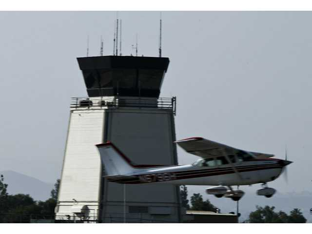 In this March 21 photo, a plane passes the control tower at Riverside Municipal Airport in Riverside. Eleven air traffic control towers at small airports throughout California are on the Federal Aviation Administration's list of nationwide facilities to be closed next month due to spending cuts.