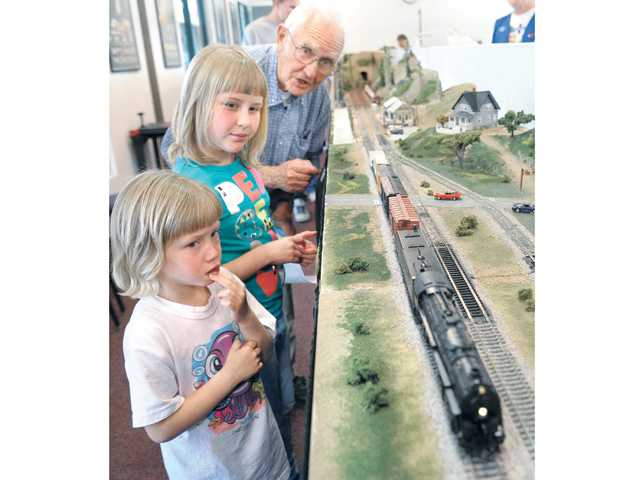 Fred Schiess and his granddaughters, Keri, 8, and Kelly, 4, admire the High Desert Modular Model Railroad Club displayat Hart Park. Signal photo by Dan Watson