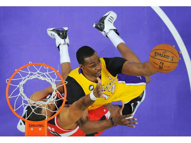 Los Angeles Lakers center Dwight Howard, right, puts up a shot as Washington Wizards center Jason Collins defends on Friday in Los Angeles.