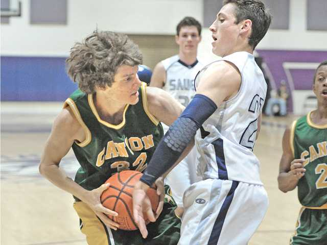 Matt Edwards (32) of Canyon High drives against Jeff Ashburn (21) of Saugus during Saturday's SCV Hoops Finale at Valencia High.