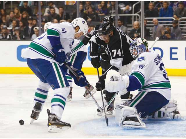Los Angeles Kings player Dwight King (74) and Vancouver Canuck Andrew Alberts (41) vie for the puck in front of the goal on Saturday in Los Angeles.