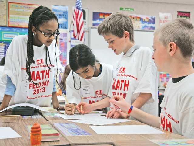 From left, Plum Canyon Elementary School fifth graders Dania Salman, Maansi Narain, Michael Kleinfeld and Cameron Nale work out a problem as part of Math Field Day for the Saugus Union School District. Some 180 children participated. Signal photo by Luke Money