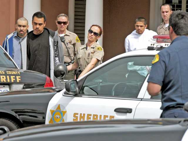 Sheriff's deputies lead three of five detainees to patrol cars outside the Residence Inn on The Old Road in Stevenson Ranch on Monday. Signal photo by Jonathan Pobre