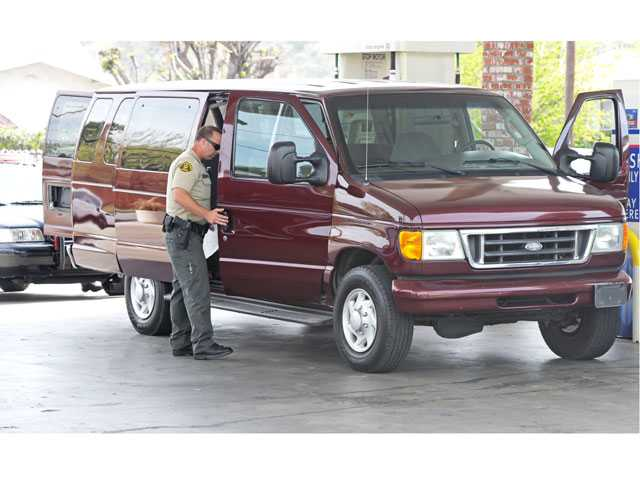 A sheriff's deputy investigates a stolen Ford van recovered in Newhall on Monday. Signal photo by Jonathan Pobre