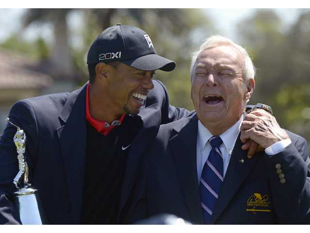 Tiger Woods, left, and Arnold Palmer share a laugh during after Woods won the Arnold Palmer Invitational in Orlando, Fla. on Monday.