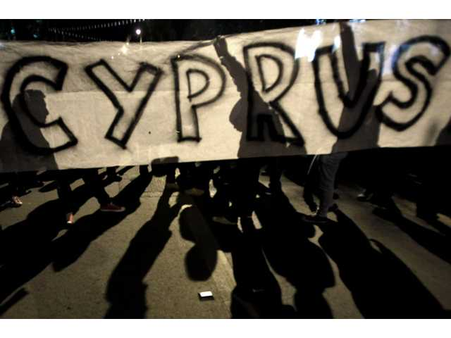 Protesters hold a banner during an anti- bailout rally outside of European Union house in capital Nicosia, Cyprus, on Sunday.