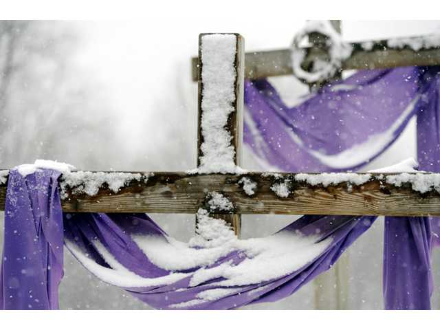 Snow accumulates on crosses at the Church of St John the Baptist in Larksville, Pa. on Monday.