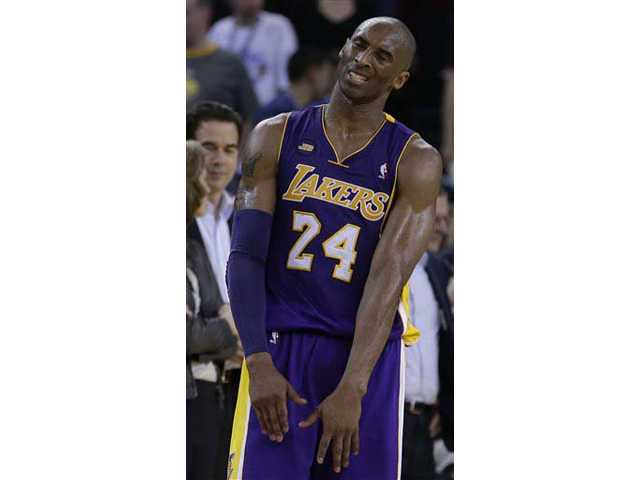 Los Angeles Lakers' Kobe Bryant reacts to missing a shot against the Golden State Warriors during the second half of an NBA basketball game Monday, in Oakland.