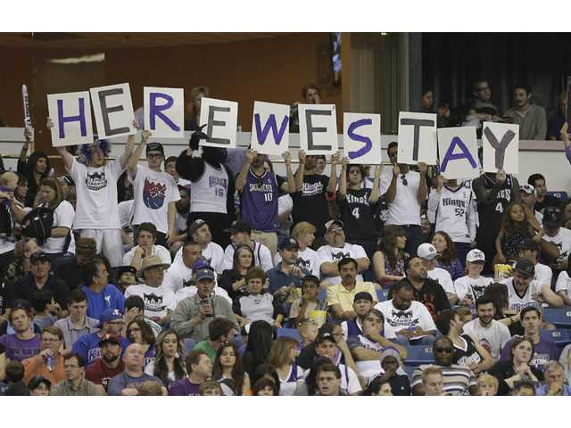 Sacramento Kings fans show support to keep the team from moving during a timeout in an NBA basketball game in Sacramento on Sunday.