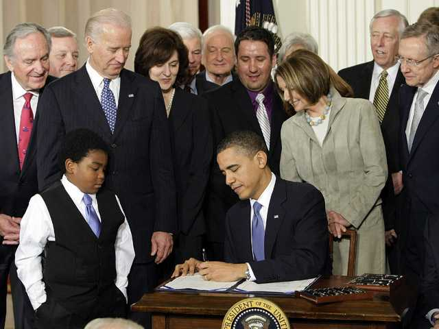 Marcelas Owens of Seattle, left, Rep. John Dingell, D-Mich., right, and others, look on as President Barack Obama signs the Affordable Care Act in the East Room of the White House in Washington, D.C. on March 23, 2010.