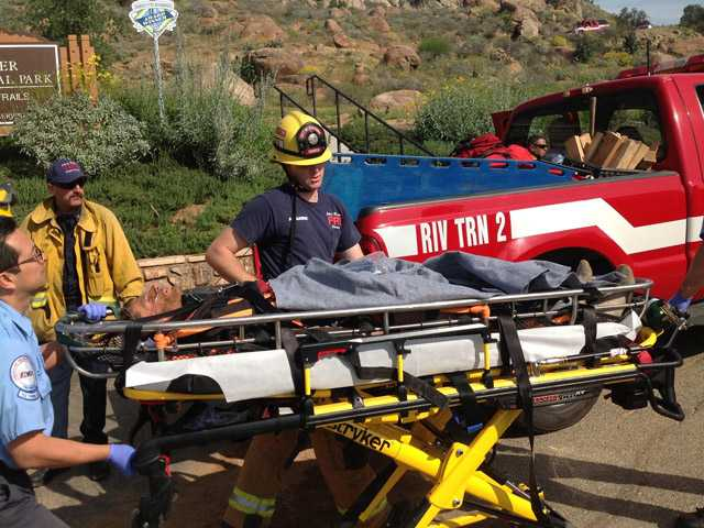 Riverside, Calif., firefighters rescue a man Monday, March 25, 2013, who was trapped in boulders on Mount Rubidoux in Southern California. Riverside fire Capt. Bruce Vanderhorst says the man is being treated Tuesday for severe dehydration. He says the man seemed confused, telling rescuers he'd been there for both a day and for five days.