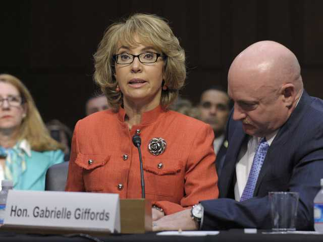 In this Jan. 30, 2012 file photo, former Arizona Rep. Gabrielle Giffords, who was seriously injured in the mass shooting that killed six people in Tucson, Ariz., in January 2011, is aided by her husband, Mark Kelly, as she speaks before the Senate Judiciary Committee hearing on gun violence on Capitol Hill in Washington.