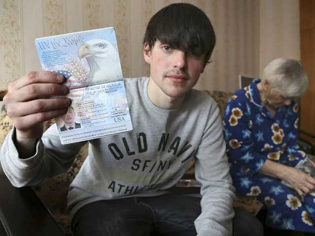 Alexander Abnosov shows his American passport to journalists in the Volga river city of Cheboksary, Russia. His 72-year-old grandmother is in the background. Abnosov was adopted by an American couple at age 12 and has returned to Russia claiming that his parents treated him badly, according to reports from Russian media with close ties to the Kremlin.
