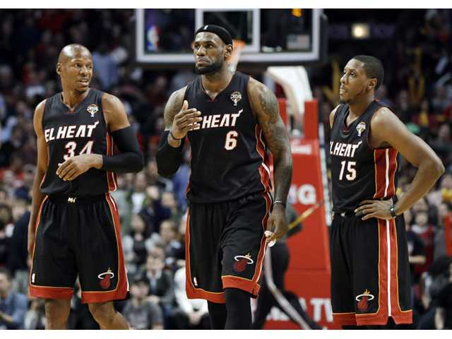 Miami Heat forward LeBron James, center, and guard Mario Chalmers, right, listen to guard Ray Allen on Wednesday in Chicago.
