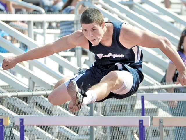Saugus' Cameron Engle clears a hurdle on Thursday at Valencia High. He won the 110 hurdles and his Saugus boys team defeated Valencia in the event.