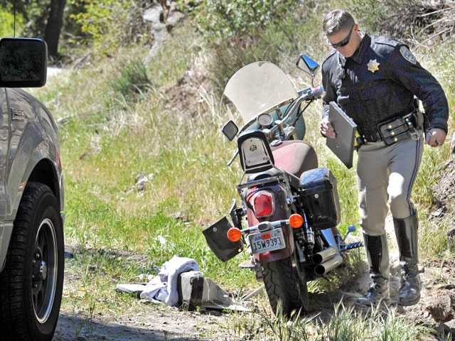 A California Highway Patrol officer investigates a crash involving a motorcycle today near the Big Oaks Lodge restaurant in the 33000 block of Bouquet Canyon Road in the Angeles National Forest. Signal photo by Jonathan Pobre