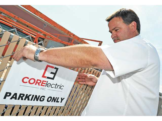 Jim Coffey places a new parking sign outside his Canyon Country office.