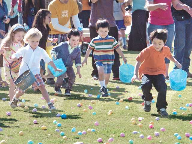 "Dan Huynh, 6, right, leads the charge as hundreds of youngsters pick up some of the thousands of plastic Easter eggs full of prizes and candy at the ""Eggstravaganza"" Easter egg hunt at Central Park in Saugus on Saturday morning. Signal photo by Dan Watson"