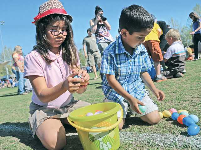 "Amanda, 9, and brother Andres Salinas, 5, of Saugus look for prizes as they open the eggs they gathered at the city of Santa Clarita ""Eggstravaganza"" held at Central Park on Saturday. Signal photo by Dan Watson"