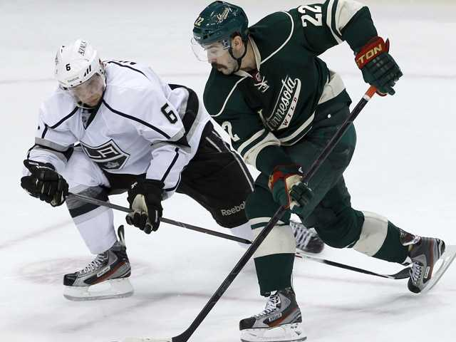 Minnesota Wild right wing Cal Clutterbuck (22) controls the puck past Los Angeles Kings defenseman Jake Muzzin (6) during overtime in St. Paul, Minn. on Saturday.