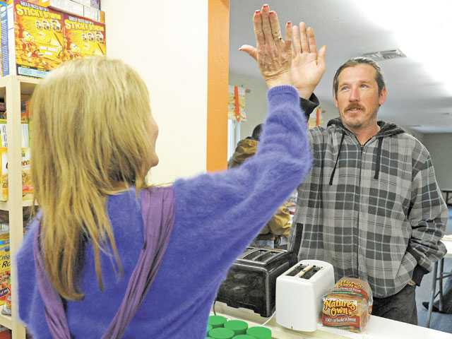 Terri Hansen of Saugus shares a high-five with Bryan Stubbins as she volunteers in the dining room of the Bridge to Home shelter on Christmas morning 2012. Signal file photo