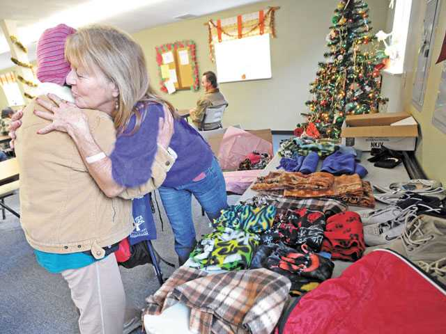 Volunteer Terri Hansen, right, offers warm clothes for Juanita Benedetti at the Bridge to Home shelter in Saugus on Christmas morning. Signal file photo