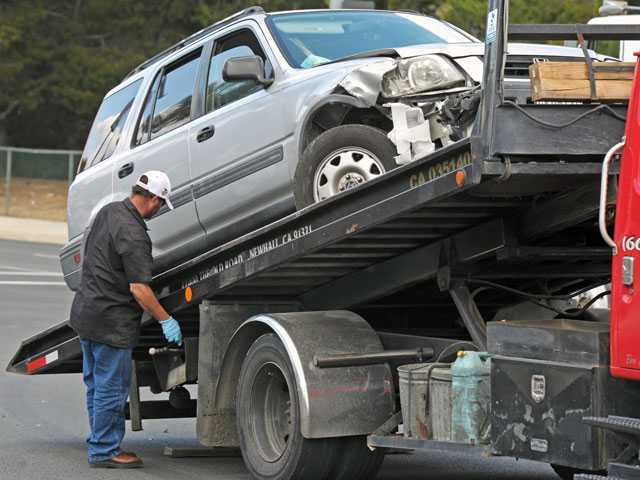 A tow truck driver moves loads a Honda CR-V involved in a two-car collision at the scene. Signal photo by Jonathan Pobre.