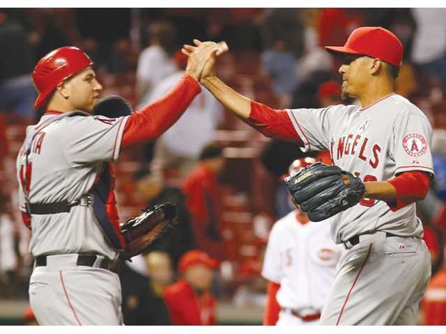 Los Angeles Angels catcher Chris Iannetta, left, congratulates relief pitcher Ernesto Frieri on Monday in Cincinnati.