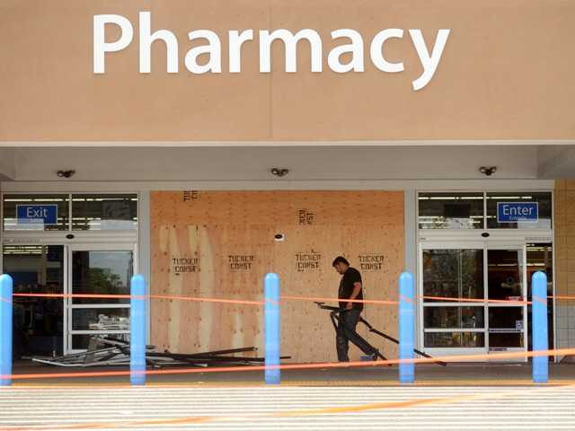 A worker cleans up damage at a Walmart in San Jose after a motorist drove through into a store and began assaulting shoppers. Four people sustained injuries.