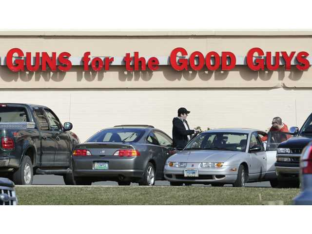 Shoppers leave Hoffman's Gun Center with their purchases in Newington, Conn. on Tuesday.