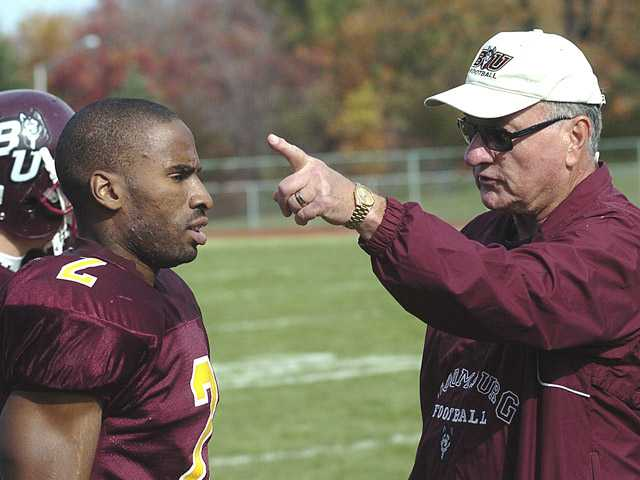 In this Nov. 3, 2007, photo, Ed Rush, right, a football coach at Bloomsburg University, talks with receiver Brahin Bilal during practice in Bloomsburg, Pa. Rush has resigned as the Pac-12 Conference's coordinator of basketball officials following comments that he targeted Arizona coach Sean Miller during internal meetings before the conference tournament.