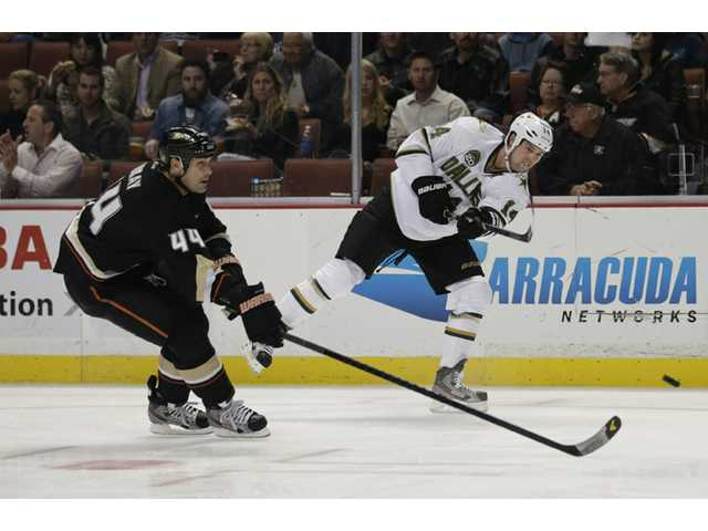 Dallas Star Jamie Benn, right, shoots as he is defended by Anaheim Duck Sheldon Souray on Wednesday in Anaheim.