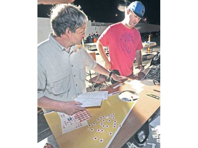 "Artists Dodd Holsapple, left, and Zach Hill use recycled game boards and stickers to create their art work themed to honor women as they participate in the ""Go Green, Get Green"" recycled art contest during the Art Slam event held on Main Street in Newhall on Thursday night."
