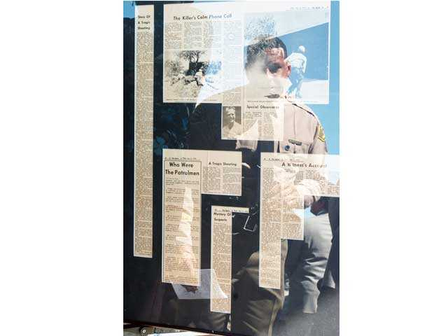 Then-Santa Clarita Valley Sheriff's Station Capt. Anthony La Berge examines newspaper clippings from the 1970 shooting of four California Highway Patrol officers during a memorial ceremony for the four in 2008. Signal file photo