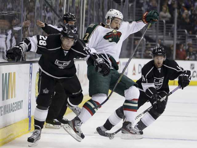 Los Angeles King Jarret Stoll, left, collides with Minnesota Wild's Cal Clutterbuck as Kings' Justin Williams, background right, controls the puck in Los Angeles on Thursday.