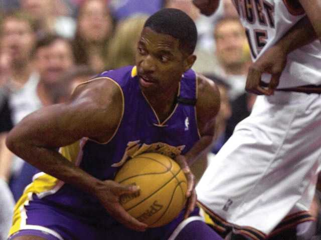 Los Angeles Lakers forward A.C. Green, left, pulls down a rebound in front of Denver Nuggets forward Keon Clark, in the first quarter March 13, 2000, at the Pepsi Center in Denver.